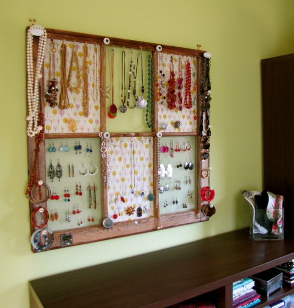 an old window frame upcycled into a jewelry organizer