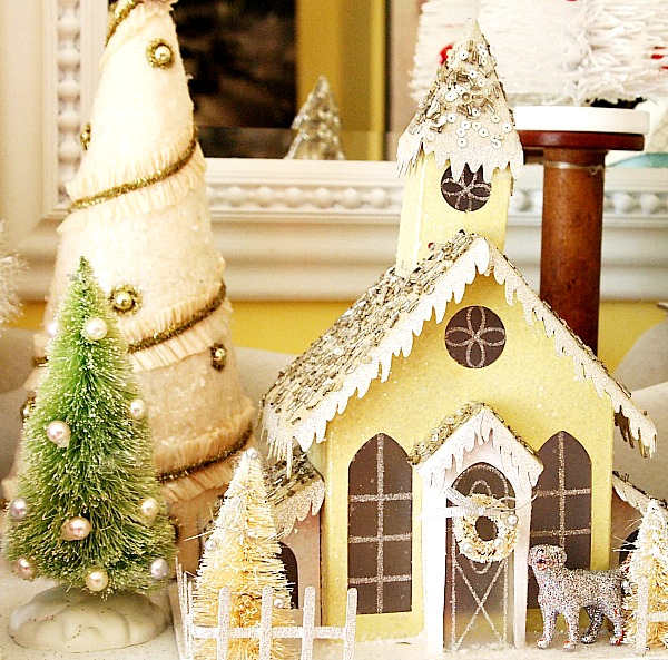 Yellow glitter house as part of a glitter house village Christmas mantel display.