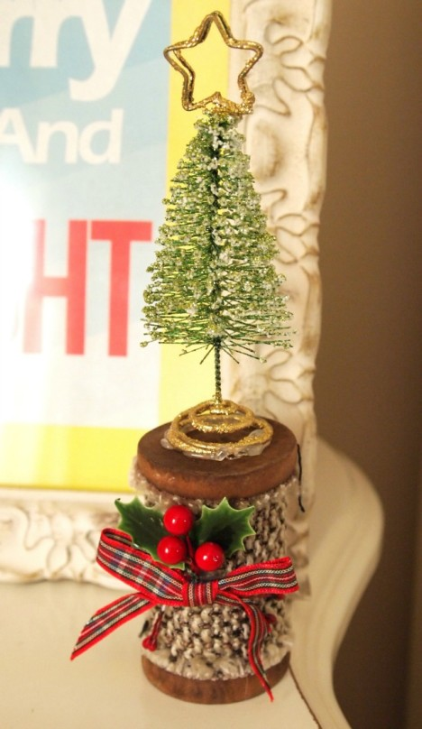 wooden spool with tree on top