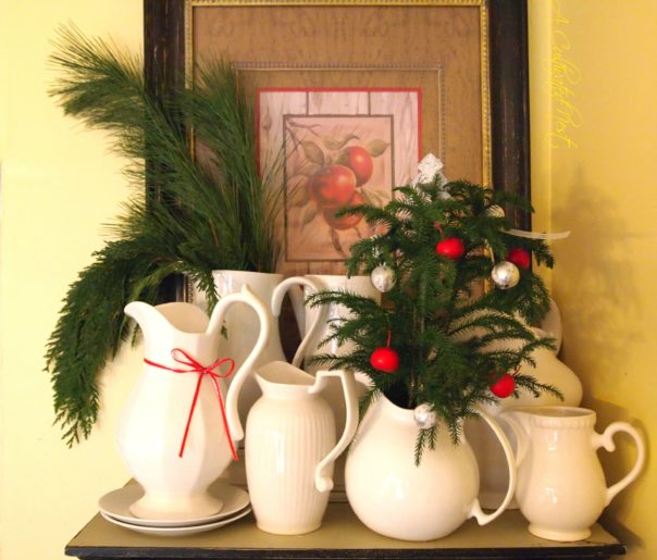 white pitchers with Christmas greenery