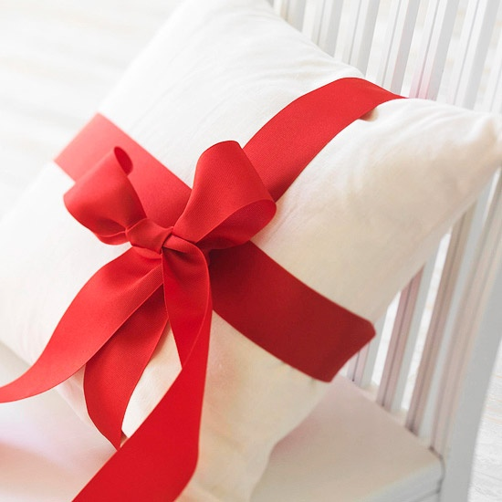 Easy Christmas Decorating Ideas like this pillow wrapped with Christmas ribbon
