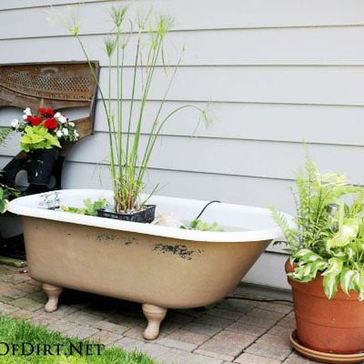 Making a Garden Pond in a Bathtub- Using an old bathtub as a container garden is easy, beautiful, and useful, too. They can hold a lot of plants and enhance your design! | upcycle bathtub, recycle bathtub, ways to use a vintage bathtub, #gardeningTips #gardenDIY #containerGarden #gardeningDIY #ACultivatedNest
