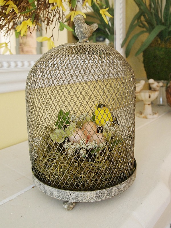 wire cloche with nest on mantel