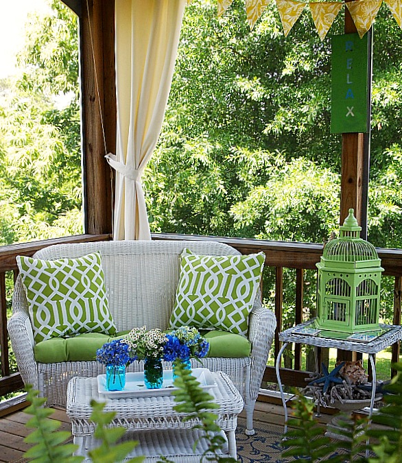 loveseat with green outdoor pillows