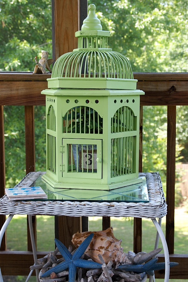 painted wooden bird cage with a plant inside
