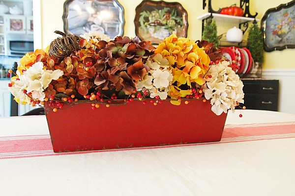 red container filled with faux hydrangeas
