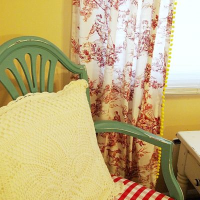 red buffalocheck chair and toile curtains