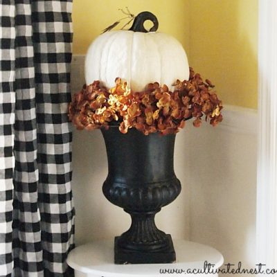 decorating with urns pumpkin in a black urn