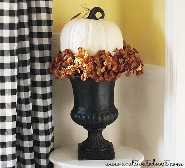 white pumpkin with fall hydrangeas in a black urn