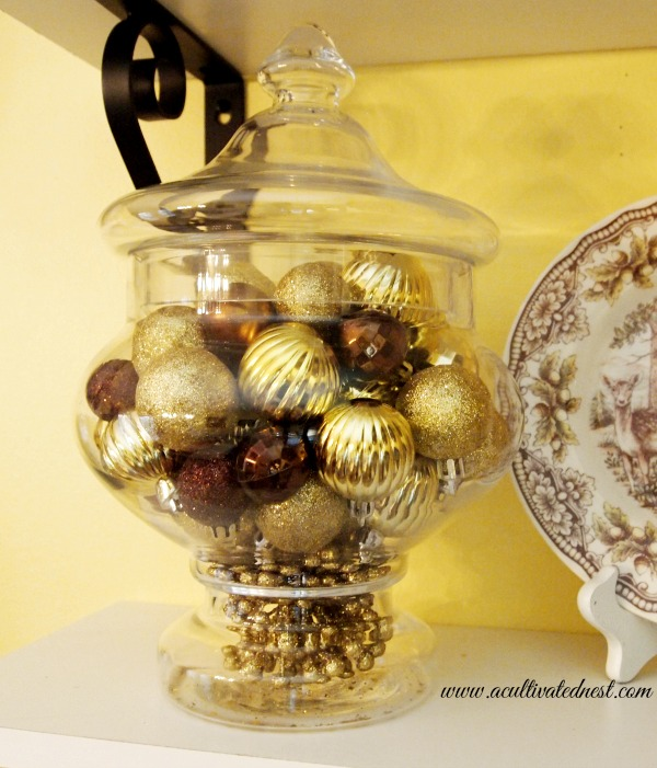 apothecary jar filled with gold and bronze Christmas ornaments