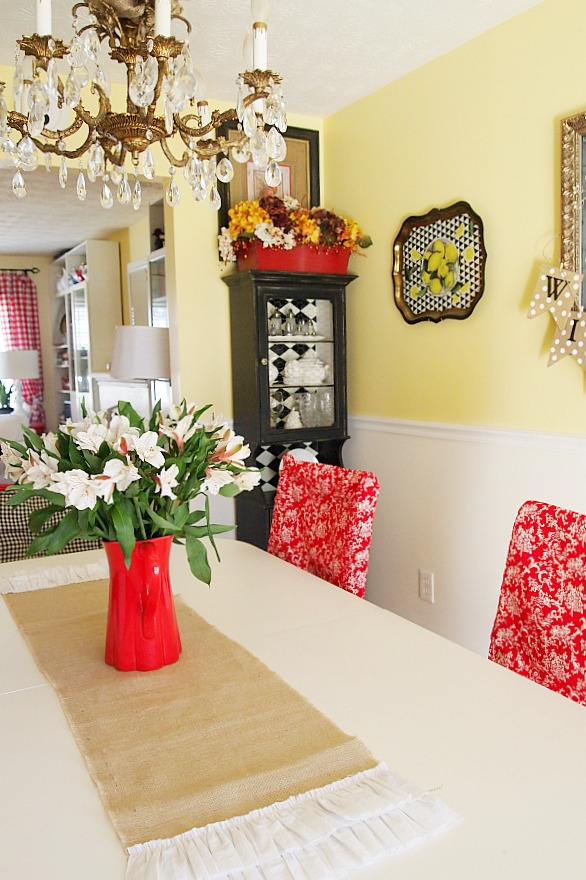 burlap runner and flowers in a red pitcher