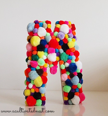 craft store letter covered with pom poms