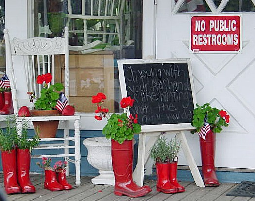 red rain boots planted with red Geraniums