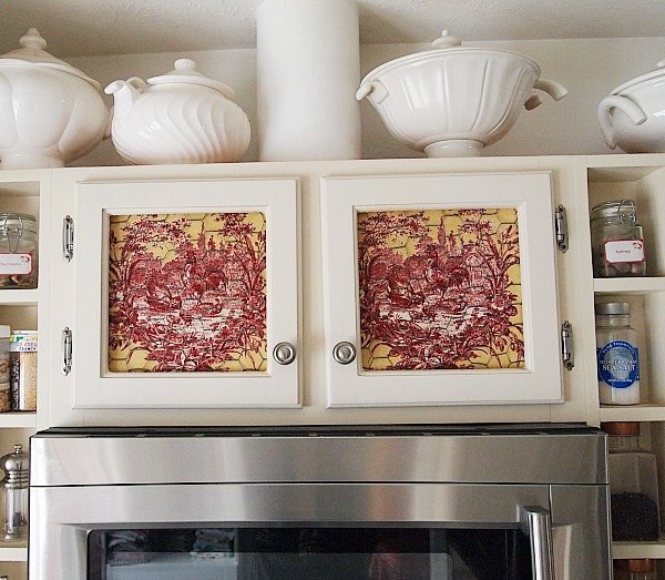 yellow & red toile fabric in kitchen cabinets behind chicken wire