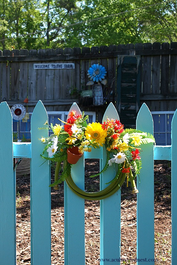 using color to unify a garden - blue garden gate and garden hose wreath