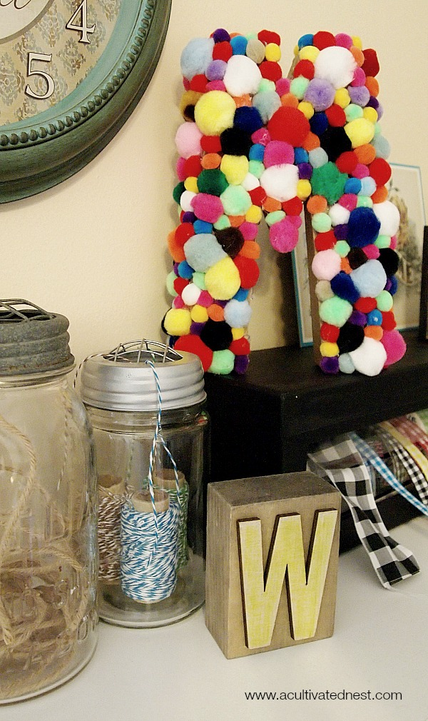 craft letter covered with pom poms