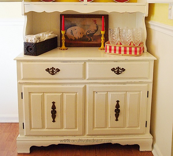 thrifted rooster prints w/yellow candle holders on a white china cabinet
