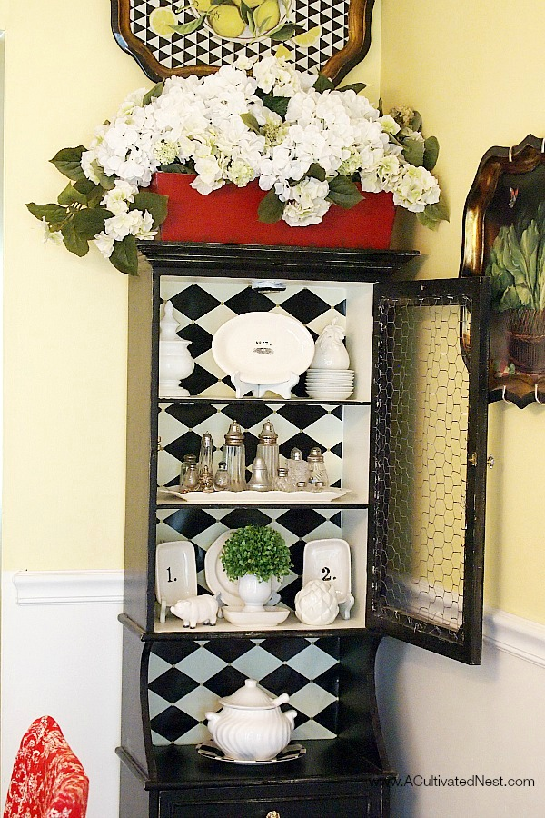 small black china cabinet filled with black and white accessories