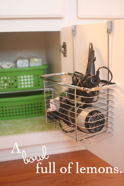 small bathroom organizing ideas: hair dryer over the door bin via A Bowl Full of Lemons (bathroom organization round up)