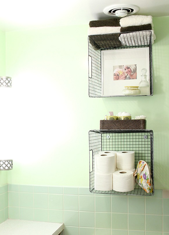 hang wire baskets on the wall for bathroom storage via A Beautiful Mess