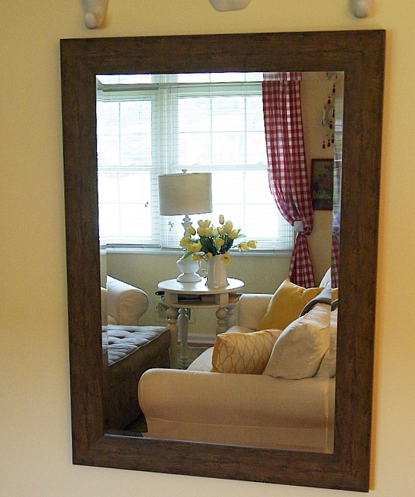 mirror reflecting part of living room