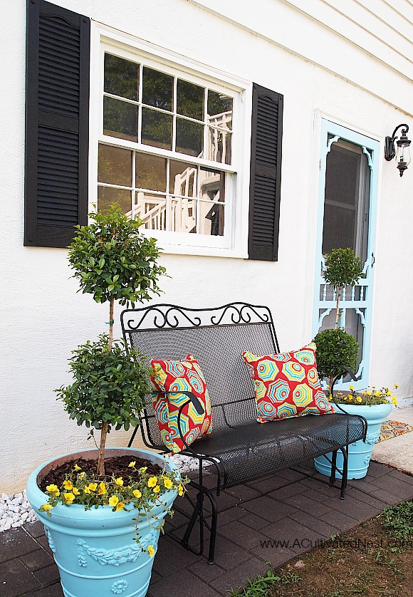 Pretty outdoor seating area by a back door -aqua screen door and containers with topiaries