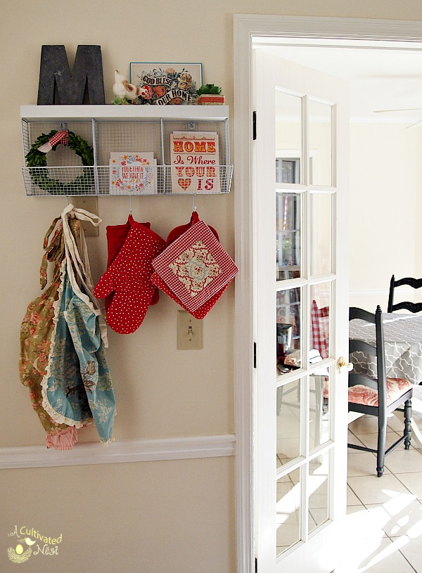Cute kitchen shelf with hooks and cubbies provides needed storage and display space in a small kitchen