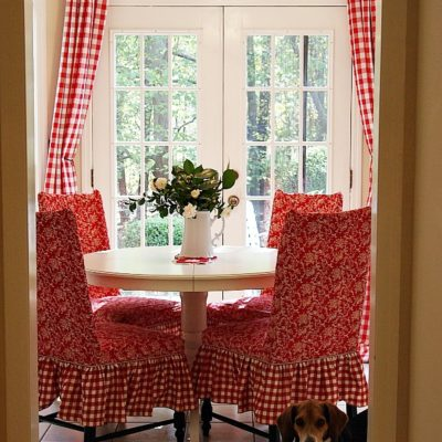 Pretty red and white dining room! Red buffalo check curtains, Ikea dining table, red slipcovered chairs