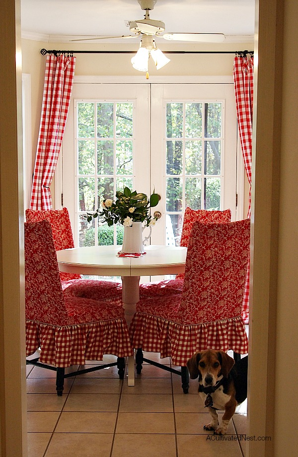 Pretty red and white dining room! Red buffalo check curtains, Ikea Liatorp dining table, red slipcovered chairs