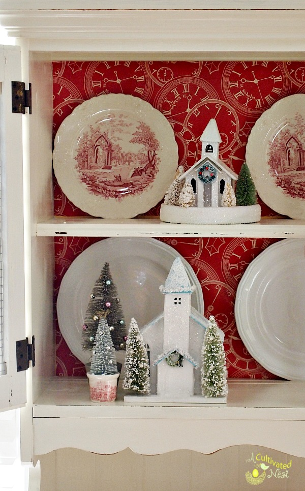 Cute Christmas china cabinet decorations!  Bottle brush trees, red transferware and glitter houses!