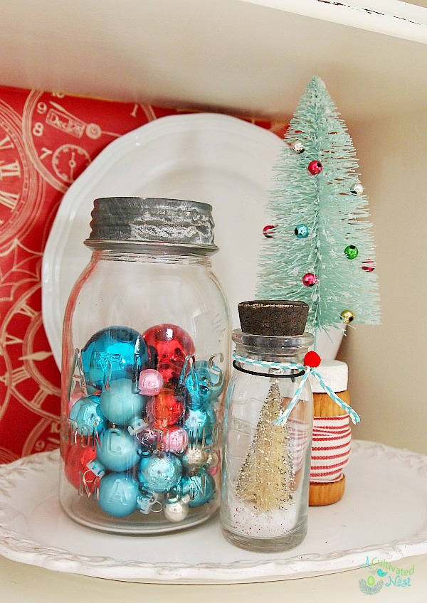 Pretty Christmas china cabinet! Vintage mason jar filled with Shiny Brites and other Christmas ornaments - easy Christmas decorating idea!