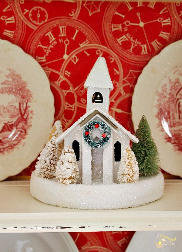 Cute Christmas china cabinet!  Church glitter house and red and white transferware on this shelf.