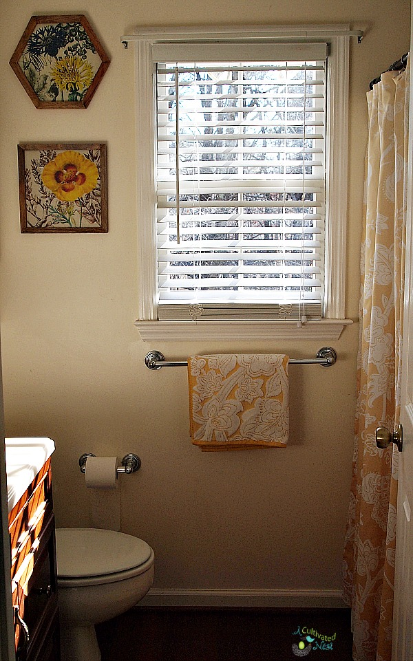 Small bathroom decorated with yellow decor items & shower curtains