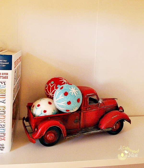 red toy truck filled with Christmas balls