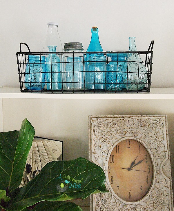 Wire basket with blue glass jars and bottle