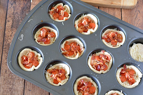 Mini Pizza Muffin Tin Appetizers- These mini pizza muffin tin appetizers are quick and easy to make, but have the flavor of a full-sized pizza! They'd make a good after-school snack, too! | New Year's Eve appetizer, New Year's recipe, party food, after-school snack, finger food, pizza bites, easy recipe