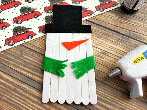 Cute Snowman Popsicle Stick Craft- An easy way to keep the kids busy this holiday season is with a fun holiday activity! You only need a couple inexpensive supplies to make this snowman popsicle stick craft! | kids craft, kids activity, winter craft, winter activity, craft sticks, easy craft