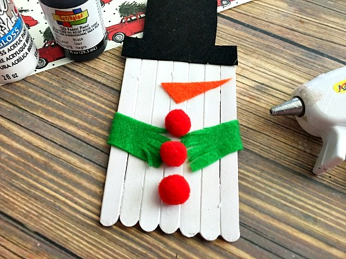 Cute Snowman Popsicle Stick Craft- An easy way to keep the kids busy this holiday season is with a fun holiday activity! You only need a couple inexpensive supplies to make this snowman popsicle stick craft!   kids craft, kids activity, winter craft, winter activity, craft sticks, easy craft