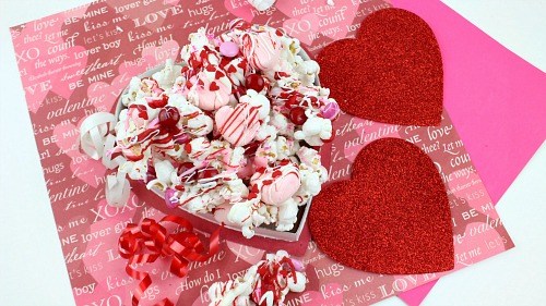 Valentine's Day Chocolate Drizzled Popcorn- This Valentine's Day chocolate drizzled popcorn is a quick and easy no-bake Valentine's treat! It'd also make a great food gift! | dessert, snack, homemade, chocolate, candy, Valentine's food gift, recipe, pink, red #ValentinesDay #popcorn #recipe #dessert