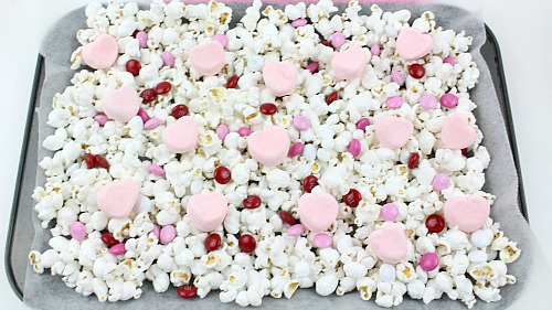 Valentine's Day Chocolate Drizzled Popcorn- This Valentine's Day chocolate drizzled popcorn is a quick and easy no-bake Valentine's treat! It'd also make a great food gift! | dessert, snack, homemade, chocolate, candy, Valentine's food gift, recipe, pink, red, white