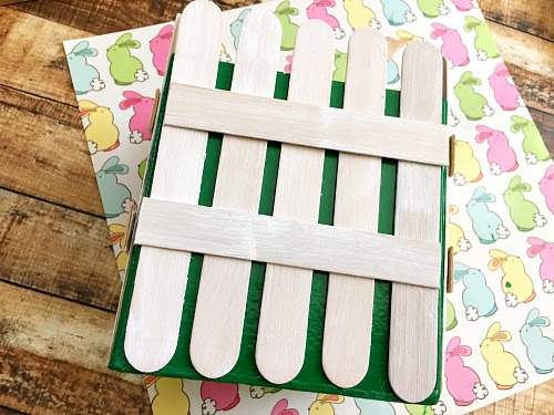 DIY Picket Fence Easter Basket- Why settle for a boring, traditional store-bought Easter basket when you can easily make this DIY picket fence Easter basket that your kids will love! | DIY project, craft idea, Easter gift basket, spring, easy DIY, inexpensive craft