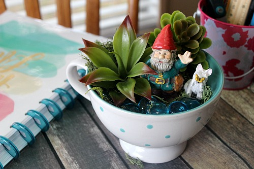 Gnome Tea Cup Fairy Garden- Need a cute decoration for your table or desk? Why not make this adorable DIY gnome tea cup fairy garden! It's easy (and inexpensive)!   DIY decor, gnome garden, cute fairy garden, faux succulents, dollar store, craft, DIY gift idea, homemade gift idea