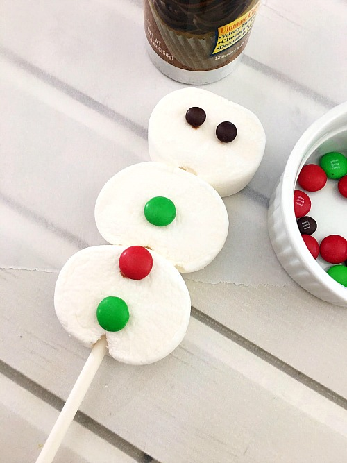 Snowman Marshmallow Pops- You don't have to go out into the cold winter weather to have fun making a snowman. Instead, make these snowman marshmallow pops! | #Christmas #snowman #dessert #recipe