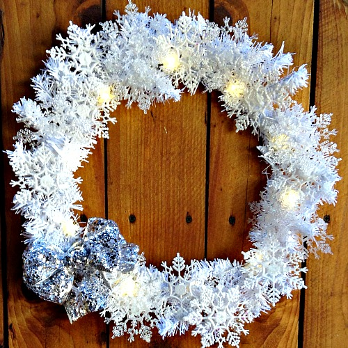 DIY Dollar Store Snowflake Wreath- It doesn't have to cost much to make your home beautiful for winter. Here's how to make a pretty, sparkly snowflake wreath with all dollar store supplies! #diy #craft #wreath #dollarStore