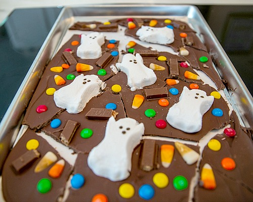 Chocolate Halloween Dessert Recipe- For a fun and easy Halloween treat, make this Halloween Milk Chocolate Boo Bark! This is also a great way to use up leftover Halloween candy! | chocolate bark with candy, recipes that use up extra Halloween candy, #Halloween #chocolate #recipe #candy #dessert #chocolateBark #ACultivatedNest