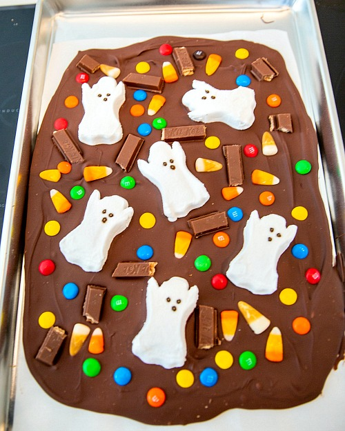 Halloween Chocolate Dessert Idea- For a fun and easy Halloween treat, make this Halloween Milk Chocolate Boo Bark! This is also a great way to use up leftover Halloween candy! | chocolate bark with candy, recipes that use up extra Halloween candy, #Halloween #chocolate #recipe #candy #dessert #chocolateBark #ACultivatedNest