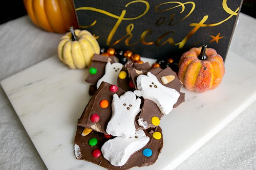 Halloween Milk Chocolate Boo Bark- For a fun and easy Halloween treat, make this Halloween Milk Chocolate Boo Bark! This is also a great way to use up leftover Halloween candy! | chocolate bark with candy, recipes that use up extra Halloween candy, #Halloween #chocolate #recipe #candy #dessert #chocolateBark #ACultivatedNest