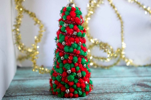 DIY Dollar Store Christmas Tree Centerpiece- Add pretty (and inexpensive) decor to your Christmas table or mantel with this DIY dollar store Christmas tree centerpiece! | Christmas craft, holiday DIY, pom pom Christmas tree, dollar store craft, #Christmas #DIY #ACultivatedNest