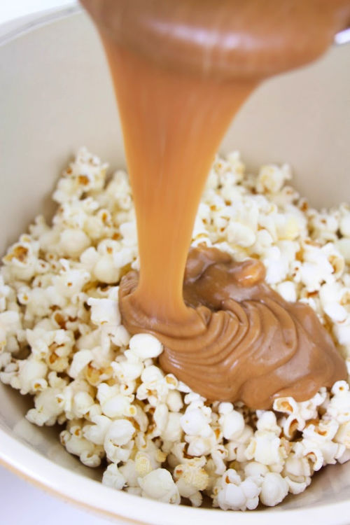 How to Make Snickers Popcorn- If you are looking for a movie night treat, this delicious homemade Snickers popcorn is what you need! It's easy to make and will win over a crowd! | way to use up leftover Halloween Candy, DIY food gifts, #popcorn #recipe #dessertPopcorn #leftoverHalloweenCandy #ACultivatedNest
