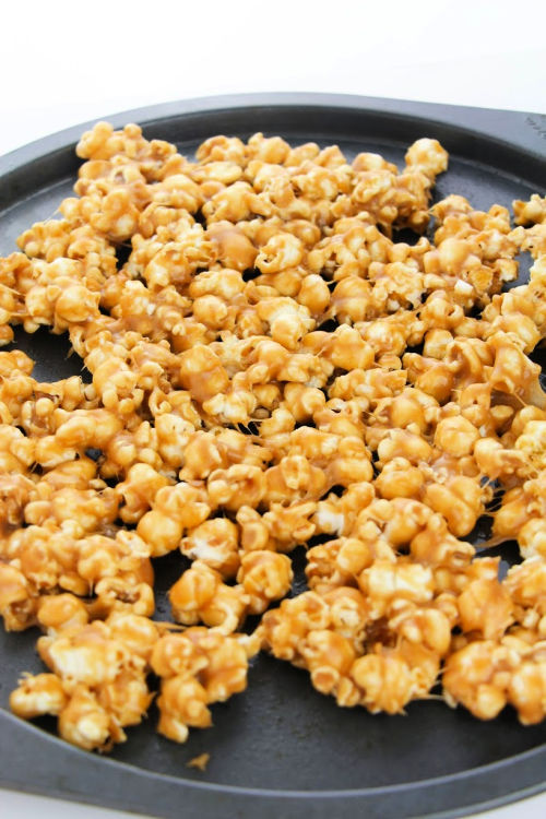 Snickers Candy Popcorn Recipe- If you are looking for a movie night treat, this delicious homemade Snickers popcorn is what you need! It's easy to make and will win over a crowd! | way to use up leftover Halloween Candy, DIY food gifts, #popcorn #recipe #dessertPopcorn #leftoverHalloweenCandy #ACultivatedNest